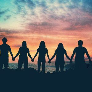 People holding hands against a sunrise sky background