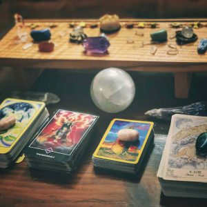 Tarot card decks and small desktop altar with crystals and stones