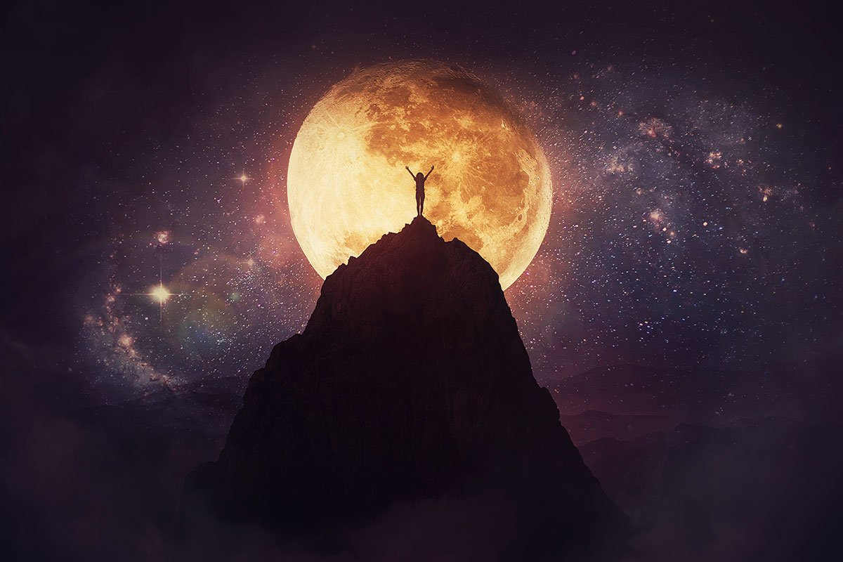 woman on mountain with hands open and full moon behind her